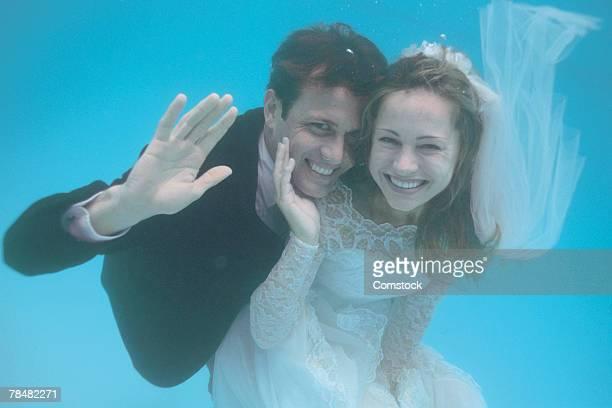 Bride and groom waving underwater