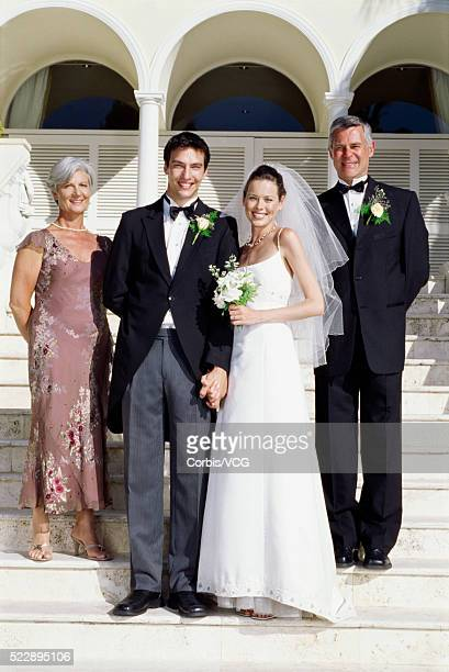 Bride and groom with their parents on stairs at wedding