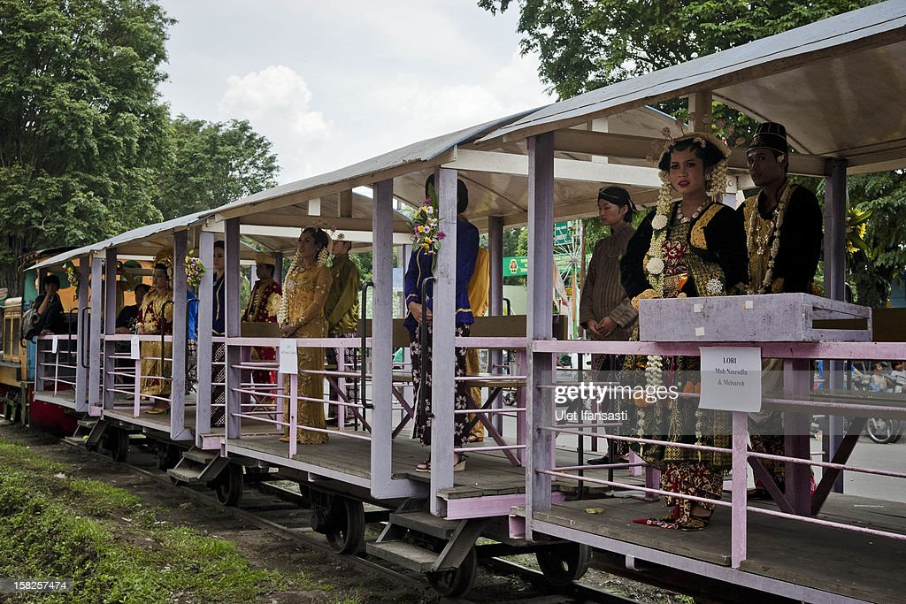 Bride and grooms ride inside a lorry train parade during a mass wedding ceremony on December 12, 2012 in Yogyakarta, Indonesia. Twelve couples participated in a mass wedding as today saw a surge in marriage across the globe to mark the once in a century date of 12/12/12.