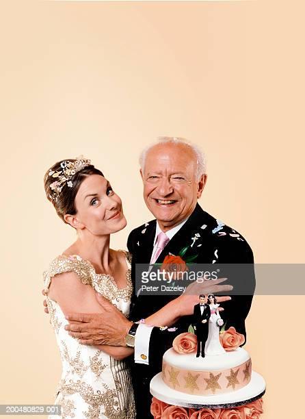 Bride and senior groom embracing next to cake, smiling, portrait