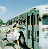 Bride and young man running to catch bus