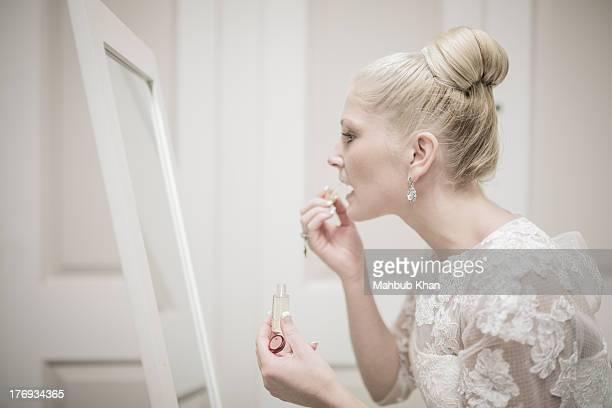 Bride applying makeup in front of mirror
