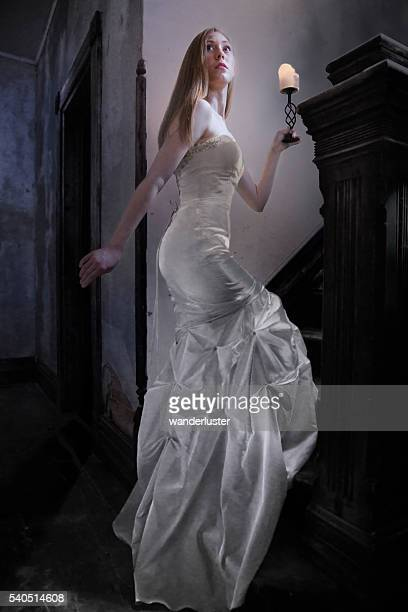bride ascends stairs in creepy old house