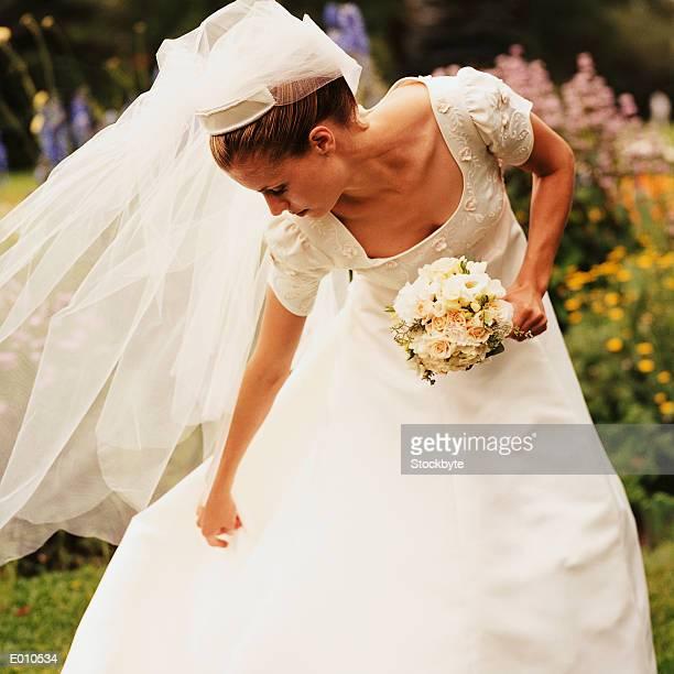 Bride bending over to adjust gown