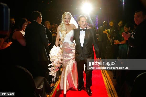 Bride Brynne Gordon and groom Geoffrey Edelsten walk down the aisle after the wedding of Geoffrey Edelsten and Brynne Gordon at Crown Palladium on...