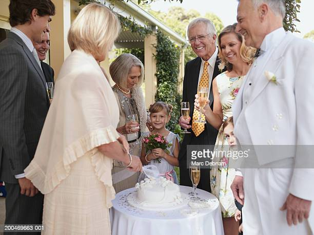 Bride cutting wedding cake, groom and guests smiling