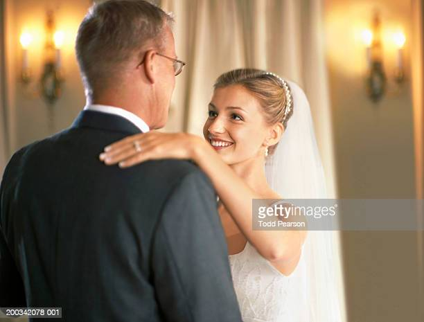 Bride dancing with father at wedding reception, smiling