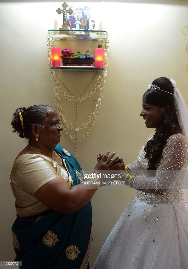 Bride Emilia D'Silva (R) jokes with her mother before leaving home for a marriage ceremony at the Mount Mary church in Mumbai on December 12, 2012. Couples may be rushing down the aisle on 12/12/12 today in hope of an auspicious union, but Brandon Pereira and Emilia D'Silva can claim an even rarer set of special dates. Brandon Pereira and Emilia D'Silva who have known each other for over 10 years now celebrated their engagement on 10/10/10, had a registered legal marriage on 11/11/11 and finally had their big white wedding in Mumbai on 12/12/12.