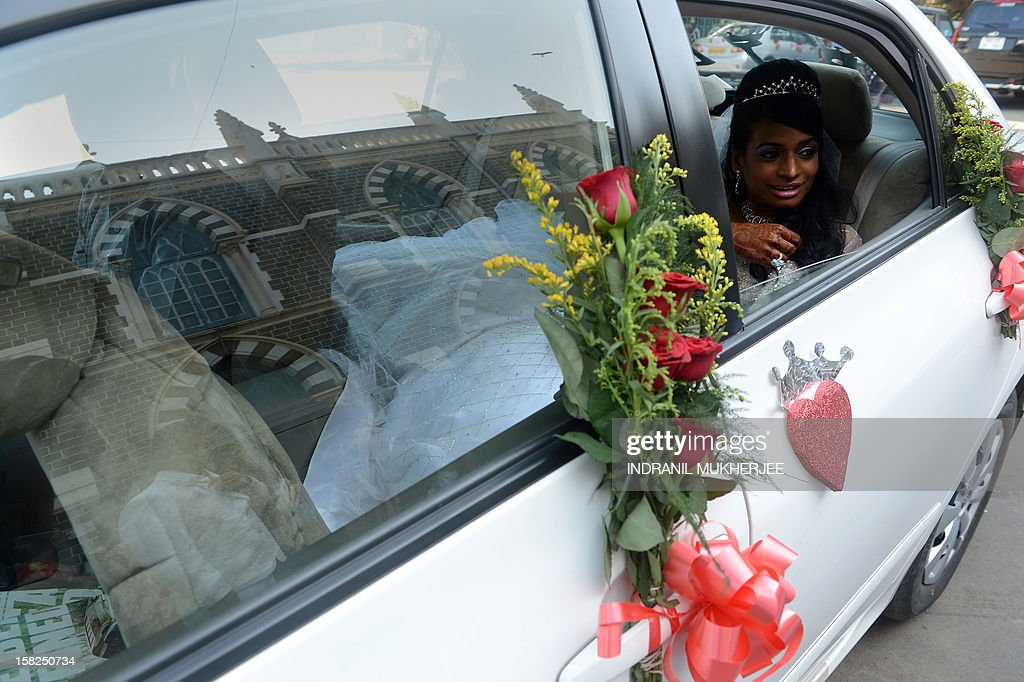 Bride Emilia D'Silva waits inside the car at the Mount Mary church in Mumbai on December 12, 2012. Couples may be rushing down the aisle on 12/12/12 today in hope of an auspicious union, but Brandon Pereira and Emilia D'Silva can claim an even rarer set of special dates. Brandon Pereira and Emilia D'Silva who have known each other for over 10 years now celebrated their engagement on 10/10/10, had a registered legal marriage on 11/11/11 and finally had their big white wedding in Mumbai on 12/12/12.