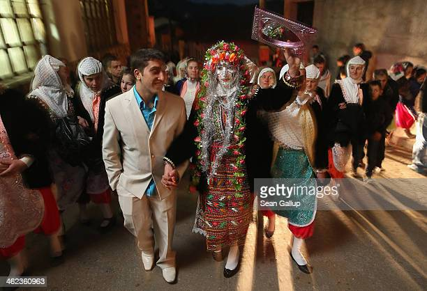 Bride Fatme Inus her face painted white and decorated with sequins holds up a mirror as she walks with her groom Mustafa Sirakov to his home...