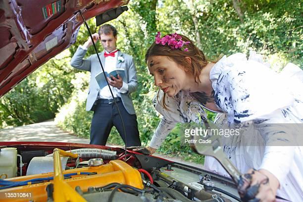 bride fixing broken down car, groom confused