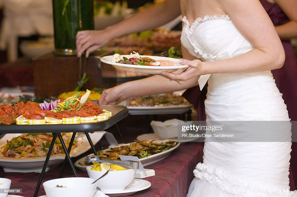 Bride getting food from buffet.
