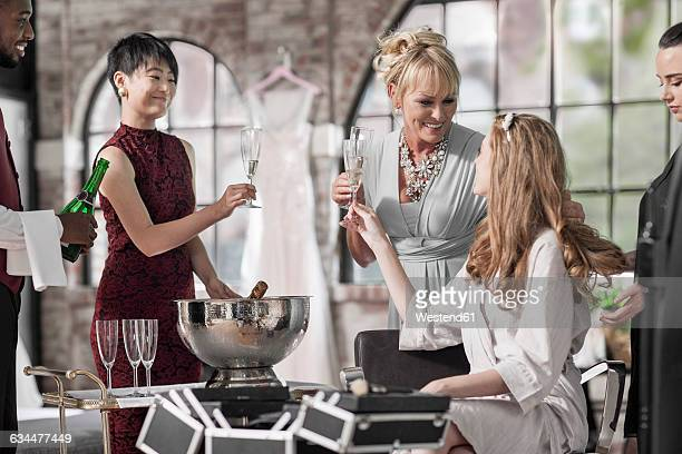 Bride getting ready for wedding clinking champagne glass with her mother
