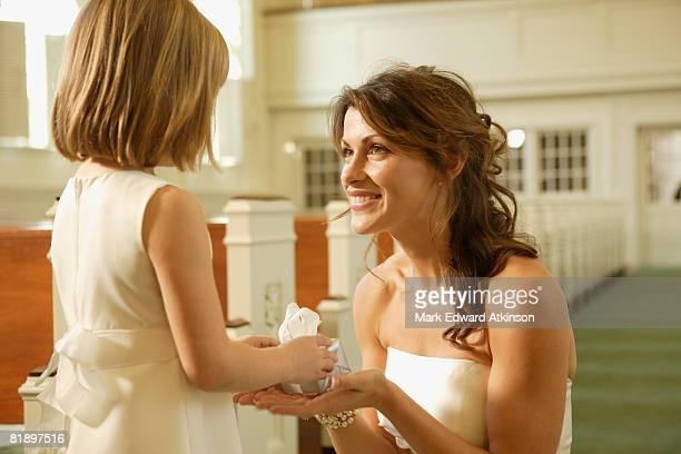 Bride giving gift to flower girl