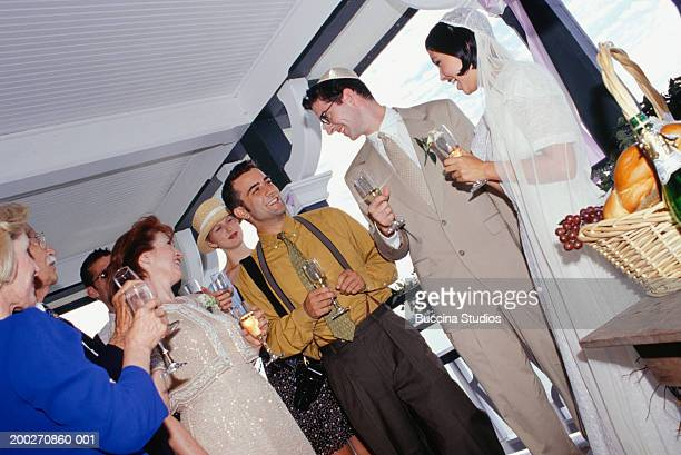 Bride, groom and guests toasting at wedding reception
