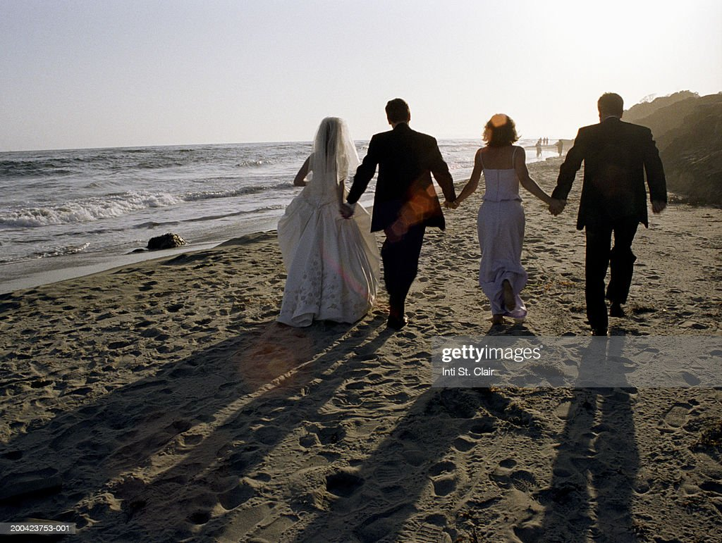 Bride, groom, bridesmaid and groomsman walking on beach, rear view : Stock Photo