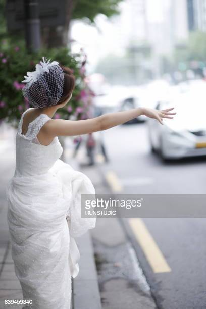 bride hitchhiking on a road