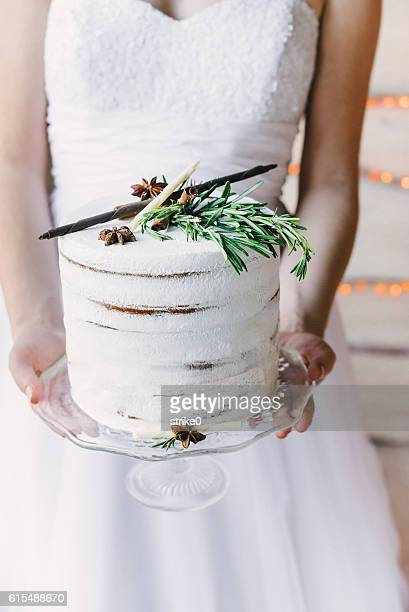 A bride holding a craft cake on a glass stand, wedding dress on the background