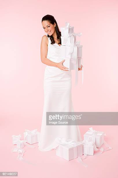 Bride holding a stack of wedding gifts