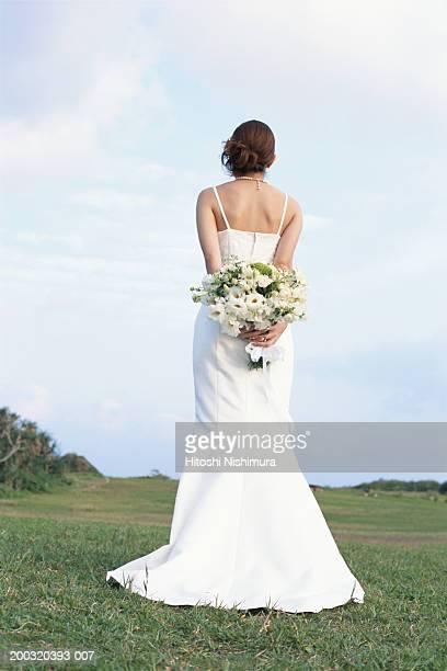 Bride holding bouquet in field, rear view