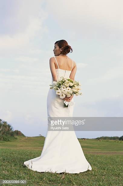 Bride holding bouquet in garden, rear view