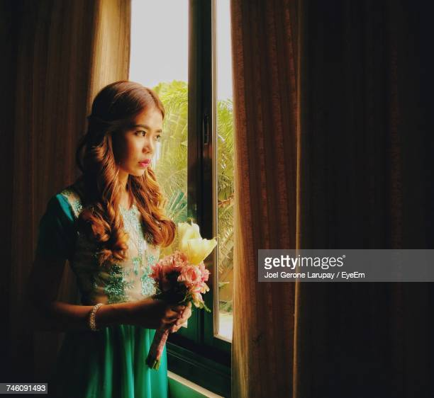 Bride Holding Bouquet Looking Through Window While Standing At Home