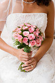 Bride holding bouquet of  pink roses