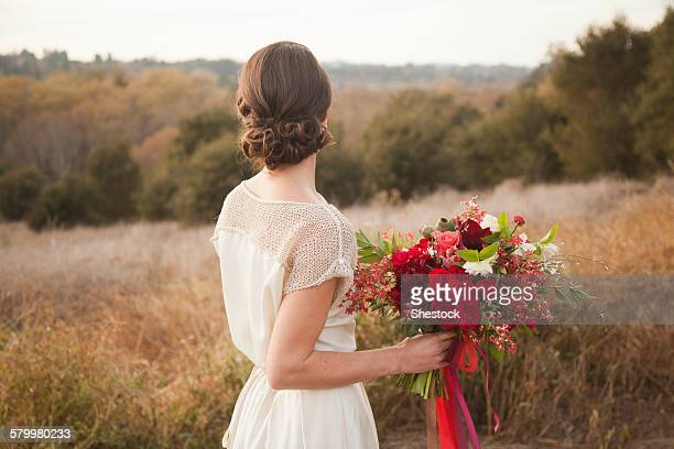 Bride holding bouquet on rural hilltop