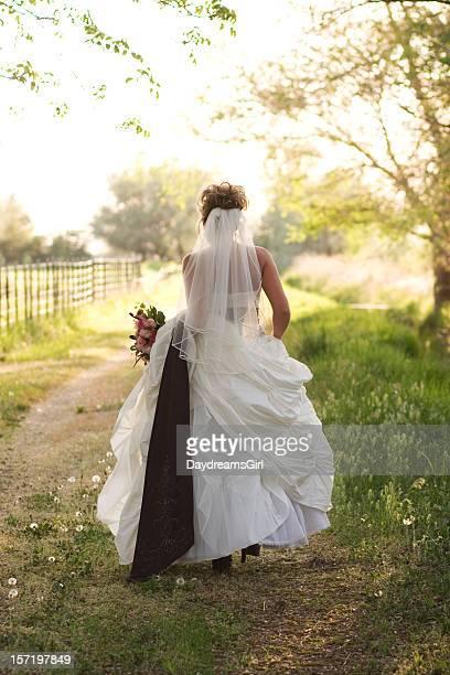 Mariée tenant robe marchant loin sur Rural Chemin de terre