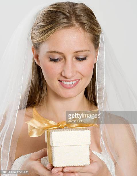 Bride holding gift box, smiling, close-up