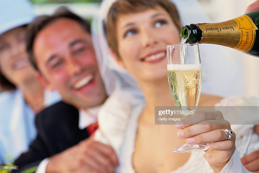 Bride holding glass being filled with champagne : Stock Photo