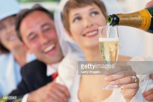 Bride holding glass being filled with champagne : Photo