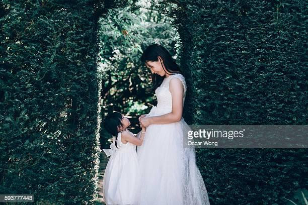 Bride holding toddler girl hands