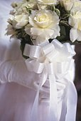 Bride holding wedding bouquet made of white roses, side view, close up, differential focus