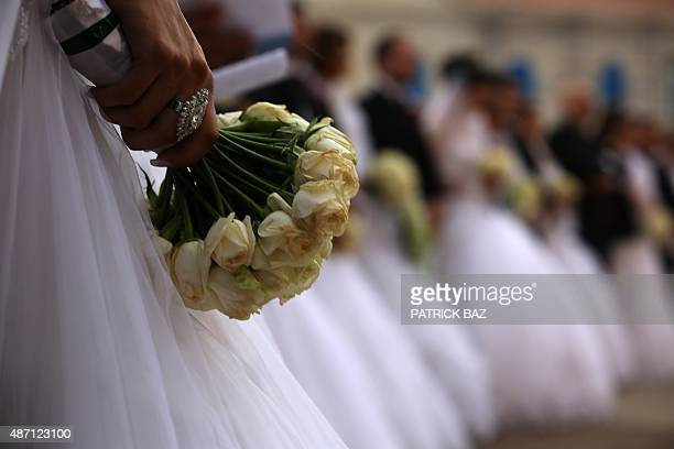 A bride holds a bouquet of flowers as Lebanese Christian couples take part in a mass wedding at the Maronite Patriarchate in Bkerke on September 6...