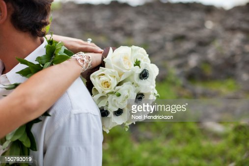 A bride holds her husband and her bouquet : Stock Photo