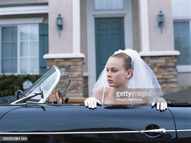 Bride in convertible car, looking away