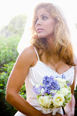 Bride in forest holding bouquet while wearing wedding dress