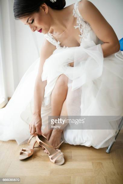 Bride in her wedding dress putting on her shoes