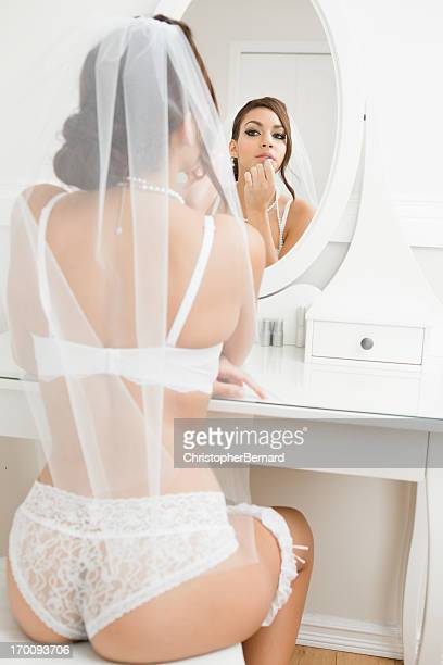Bride in lingerie putting on lipstick