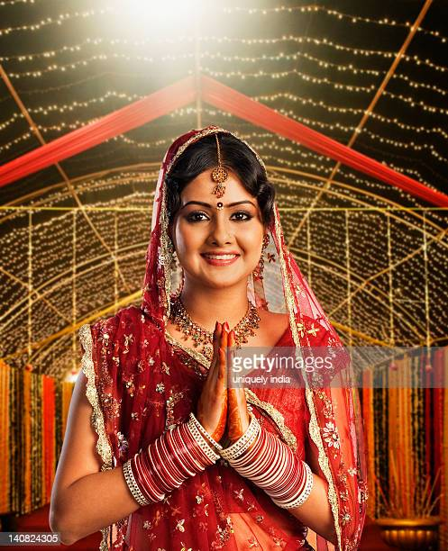 Bride in traditional wedding dress and making greeting gesture