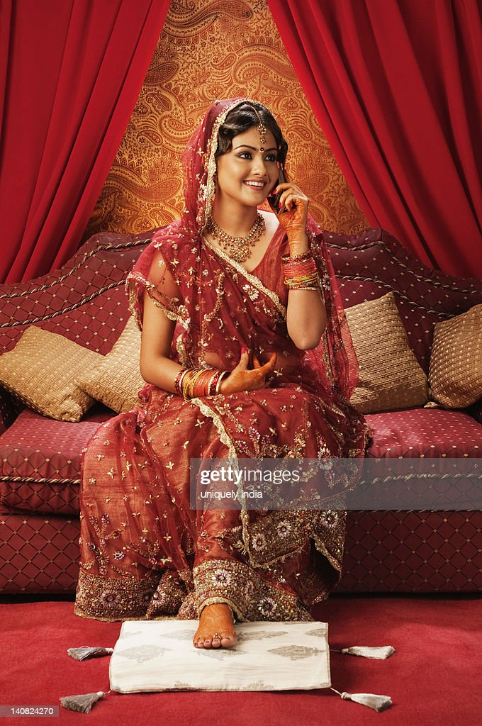 Bride in traditional wedding dress and talking on a mobile phone : Stock Photo