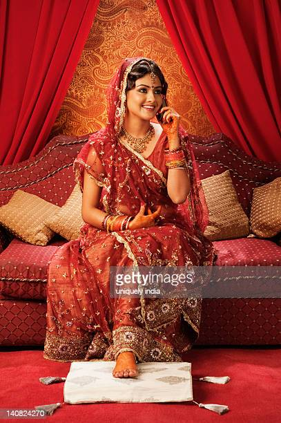 Bride in traditional wedding dress and talking on a mobile phone