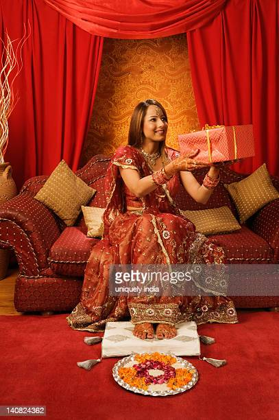 Bride in traditional wedding dress holding a gift