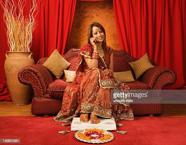 Bride in traditional wedding dress talking on a mobile phone