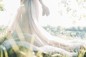 Bride in a wedding dress holds shoes against the sun. fine art photography