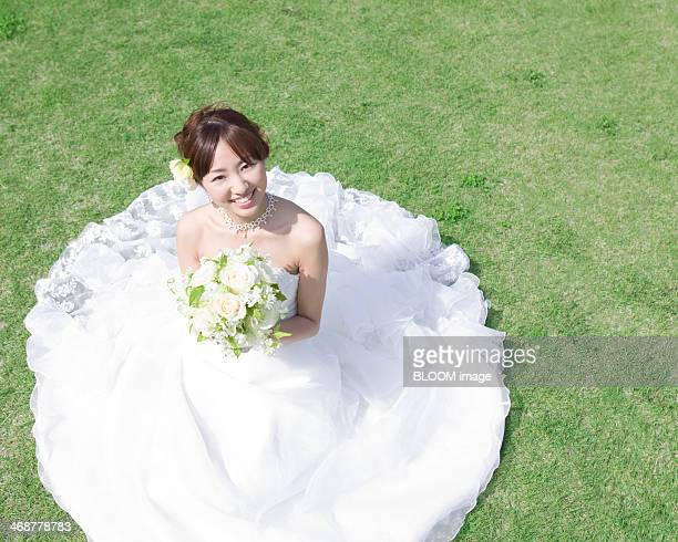 Bride In Wedding Dress Sitting On Ground