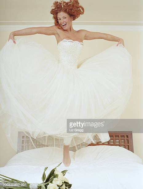 Bride jumping on bed holding out net skirts, smiling, portrait