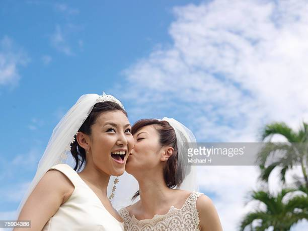 Bride kissing another bride under blue sky, low angle view