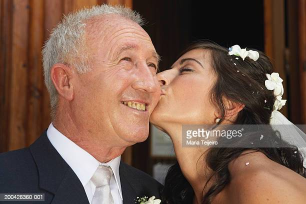 Bride kissing father on cheek, close-up
